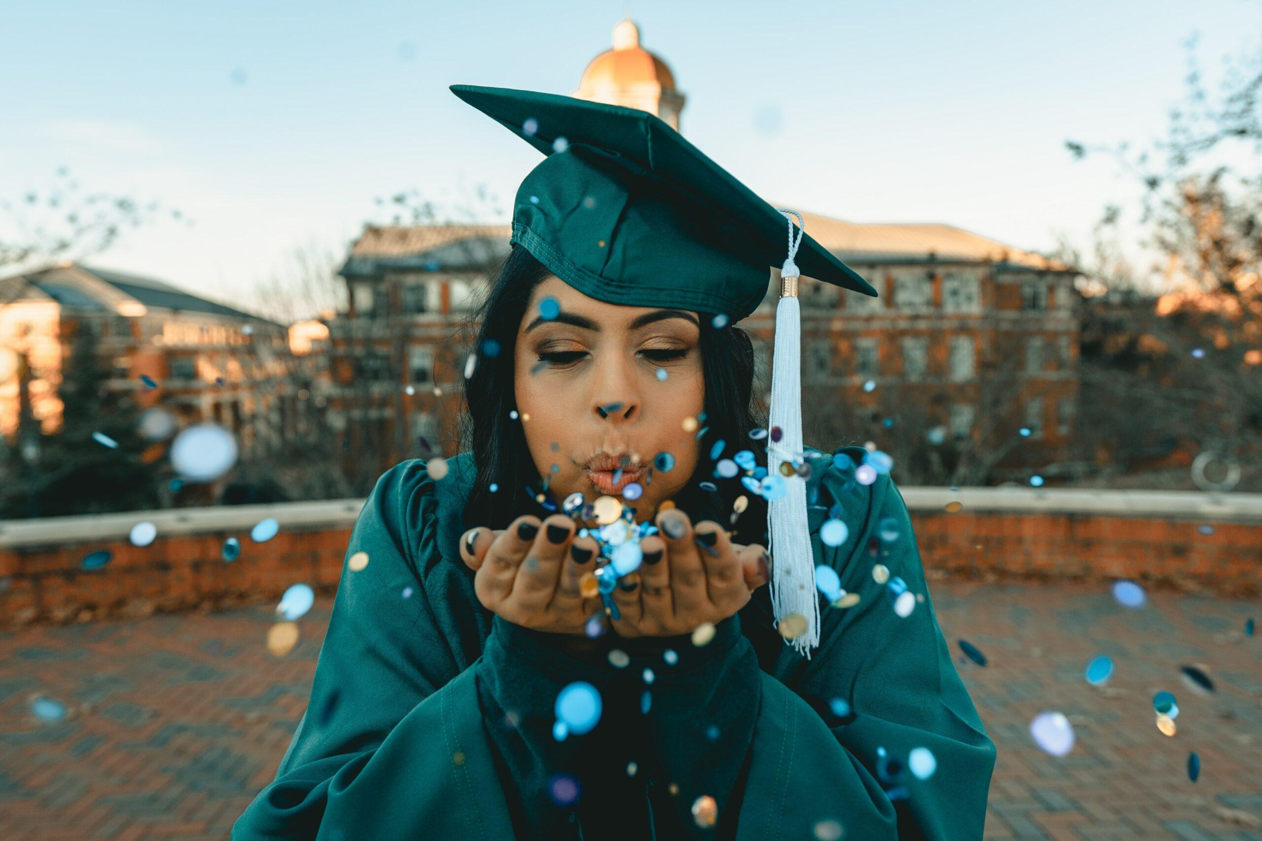 Woman in graduate's cap blowing confetti toward the camera
